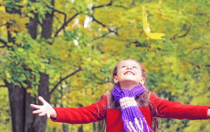 小女孩画象有胳膊的在秋天公园伸出户外 库存照片