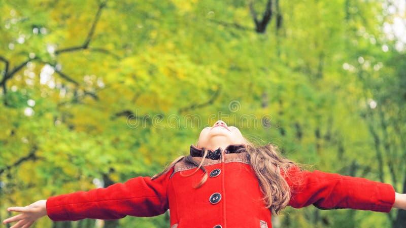 小女孩画象有胳膊的在秋天公园伸出户外 免版税库存图片