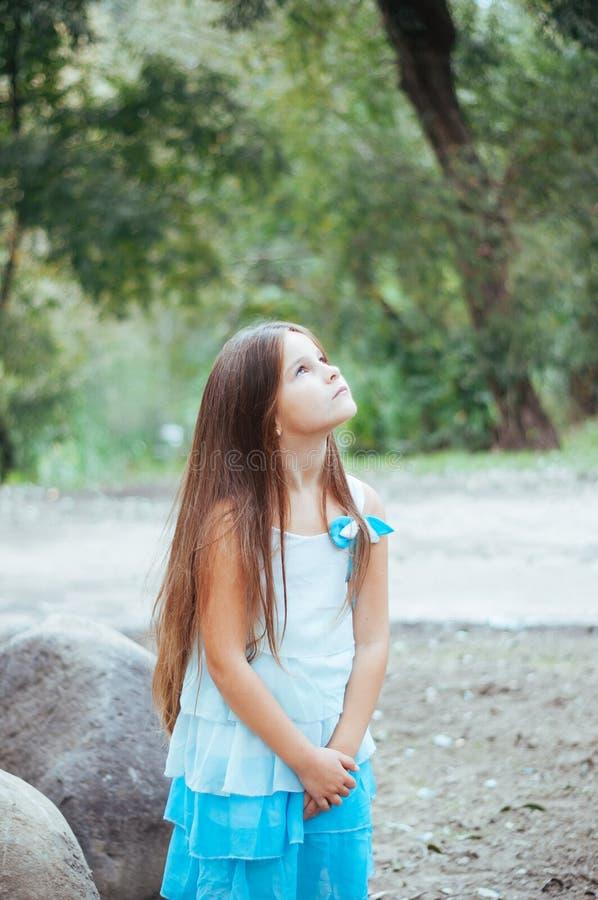 小女孩画象,直接地坐和观看,自然照明设备外面 免版税图库摄影
