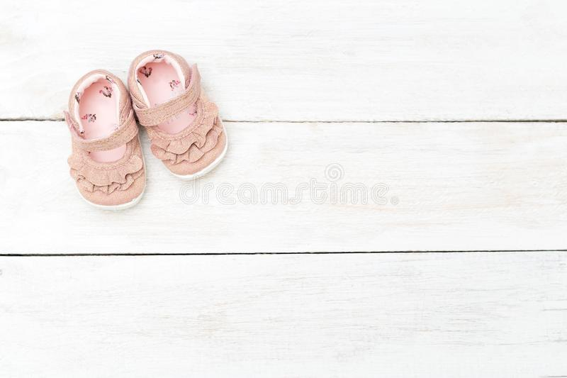 小女孩的桃红色鞋子白色木背景的 复制sp 免版税库存照片
