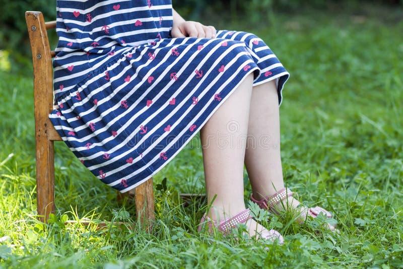 小女孩的腿和脚礼服的坐在gree的一把椅子 图库摄影
