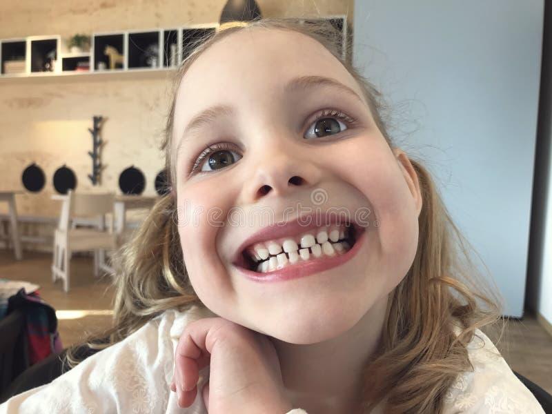 小女孩的滑稽的面孔有白色牙的 免版税库存照片