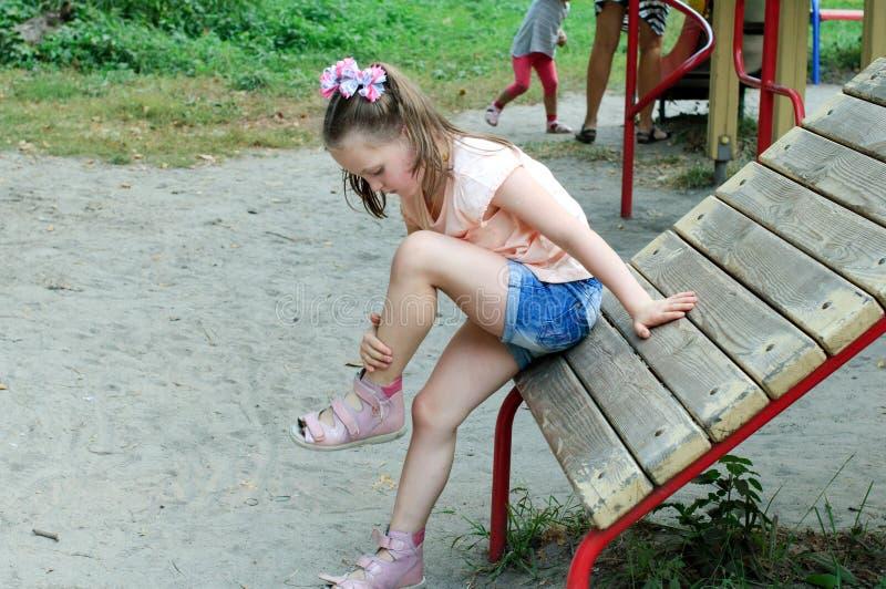 小女孩看她的挫伤 免版税库存图片
