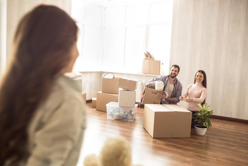 小女孩看给她的父母 年轻人和妇女打开他们新的家的箱子并且看对他们 免版税库存照片