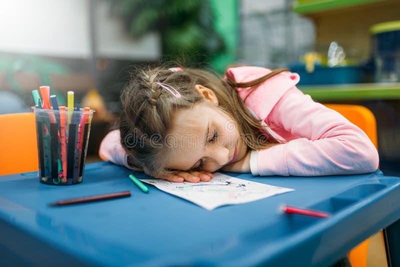 小女孩睡眠在玩耍区域,宠物店 免版税图库摄影