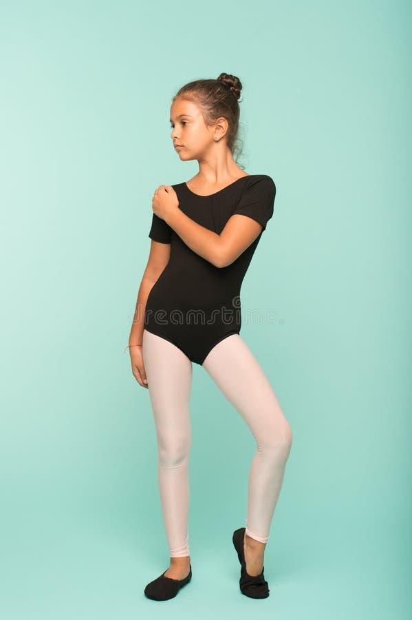 小女孩研究跳舞在舞蹈学校 小女孩有舞蹈课 雍容和秀丽 她在完善的状态 图库摄影
