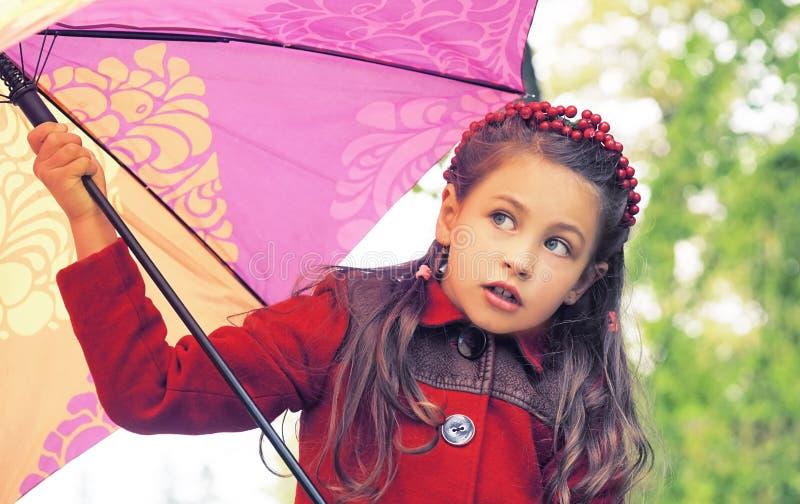 小女孩秋天画象有站立户外在公园的五颜六色的伞的 免版税图库摄影