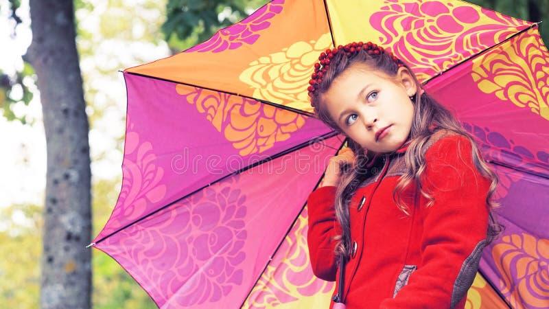 小女孩秋天画象有站立户外在公园的五颜六色的伞的 免版税库存照片