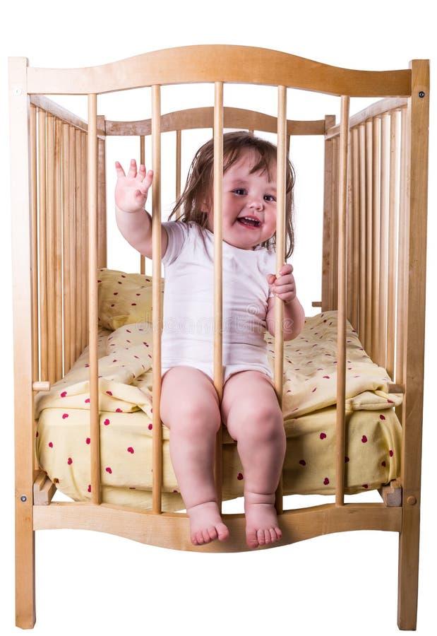 小女孩笑的坐在床上 库存图片