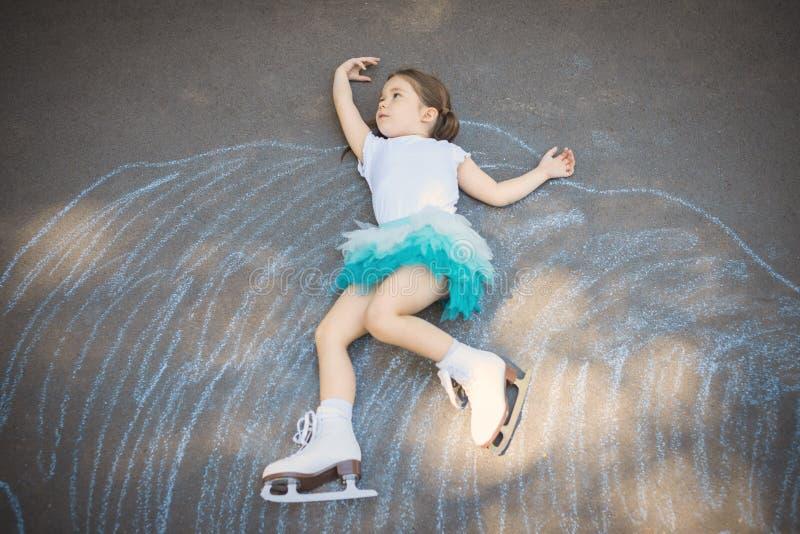 小女孩花样滑冰在虚构的滑冰场竞技场 免版税库存照片