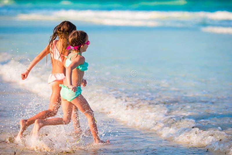 小女孩获得乐趣在热带海滩在一起使用在浅水区的暑假时 免版税库存图片