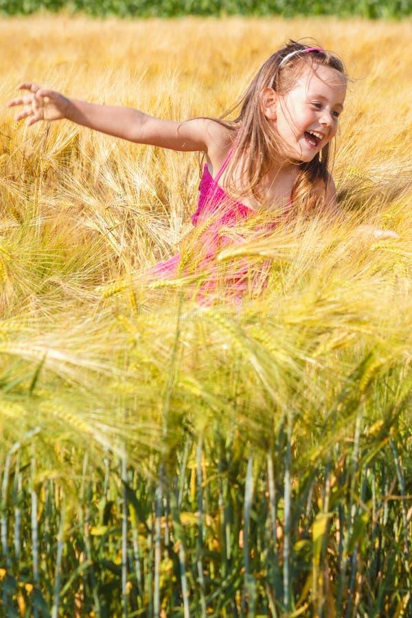 小女孩获得乐趣在麦田 免版税库存照片