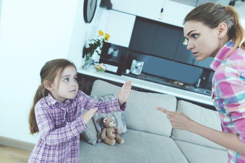 小女孩被吓唬并且被保护免受看顾 她诅咒女孩并且威胁她与手指 库存图片