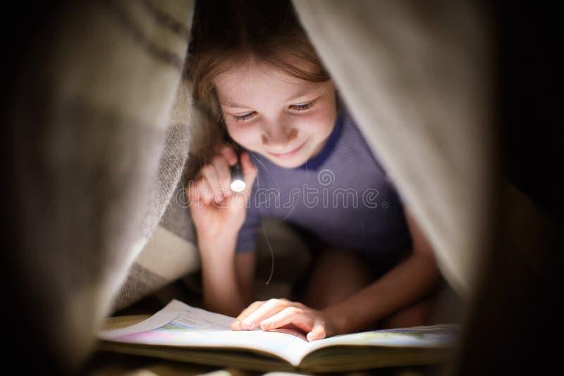 小女孩读一本书在有一个手电的一条毯子下在一个暗室在晚上 库存图片