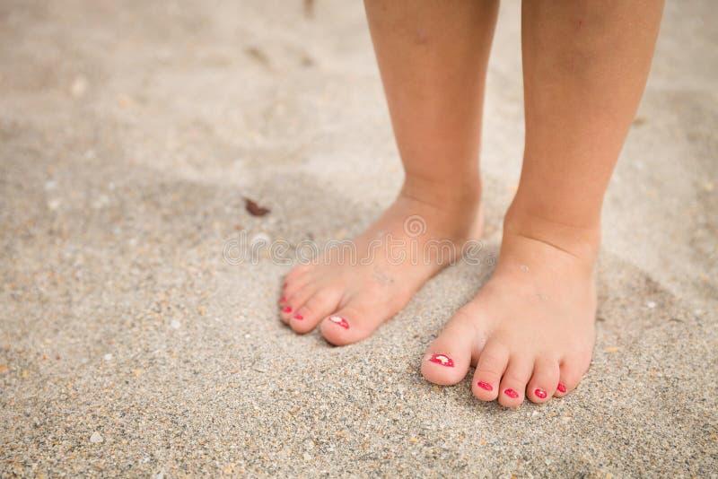 小女孩走在海滩的沙子的` s腿和脚的特写镜头与海水的在背景夏天 免版税图库摄影