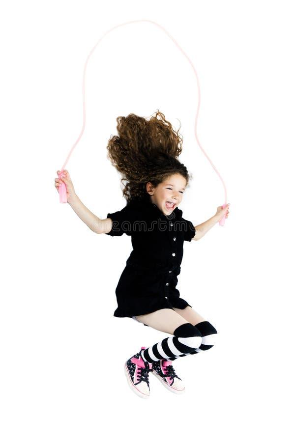 小女孩跳跃的跨越横线 免版税库存图片