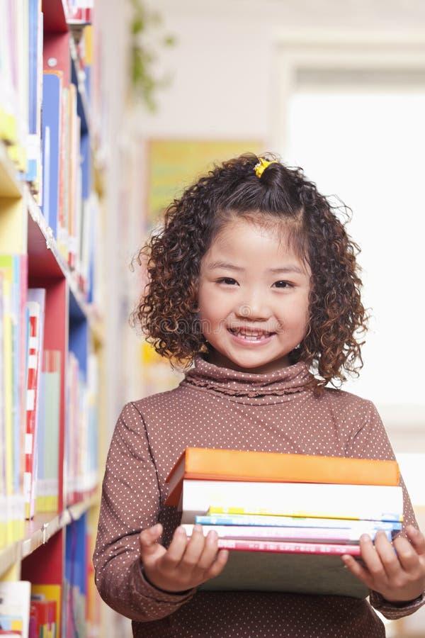 小女孩运载的书 免版税库存图片