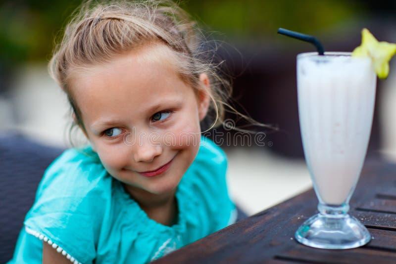 小女孩饮用的圆滑的人户外 免版税图库摄影