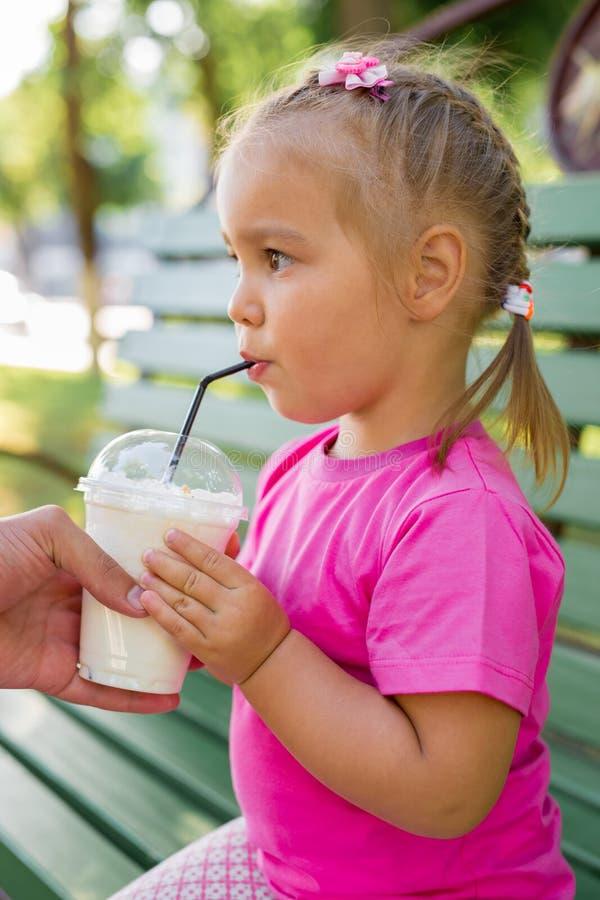 小女孩饮用的奶昔通过秸杆 库存照片