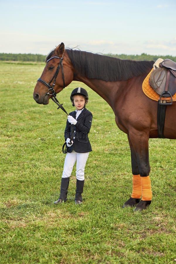 小女孩骑师由它的马勒的主角马横跨专业成套装备的国家 免版税库存图片