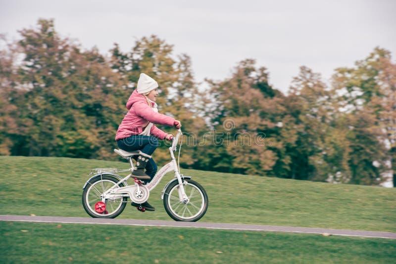 小女孩骑马自行车在公园 免版税库存照片