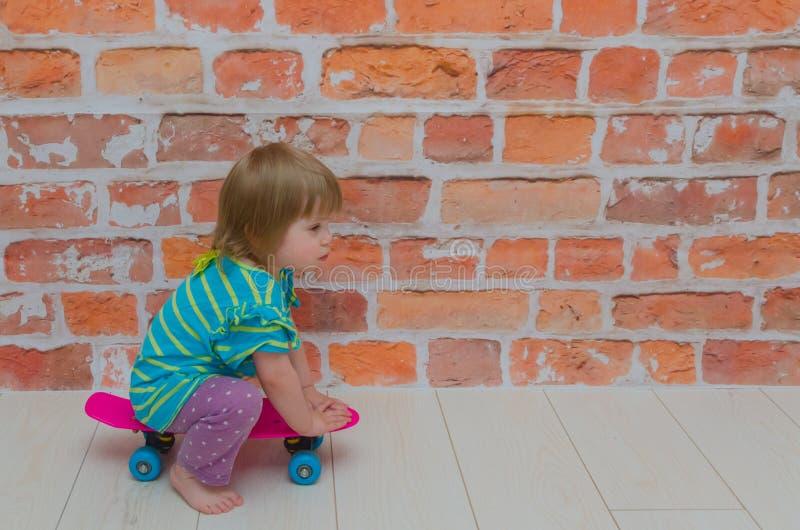 小女孩,乘坐滑板的孩子在砖墙backgroun 免版税库存图片