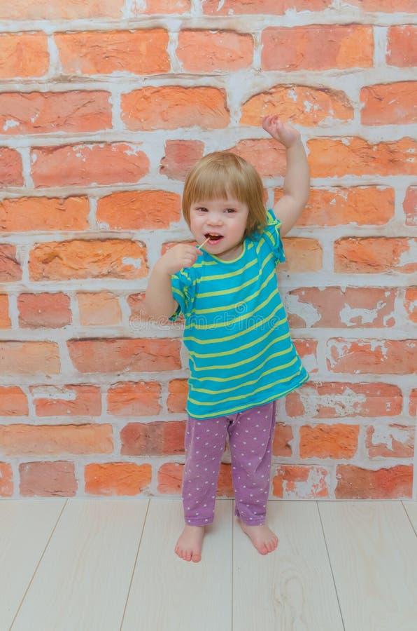 小女孩,婴孩用在棍子的糖果,在砖墙背景 免版税图库摄影