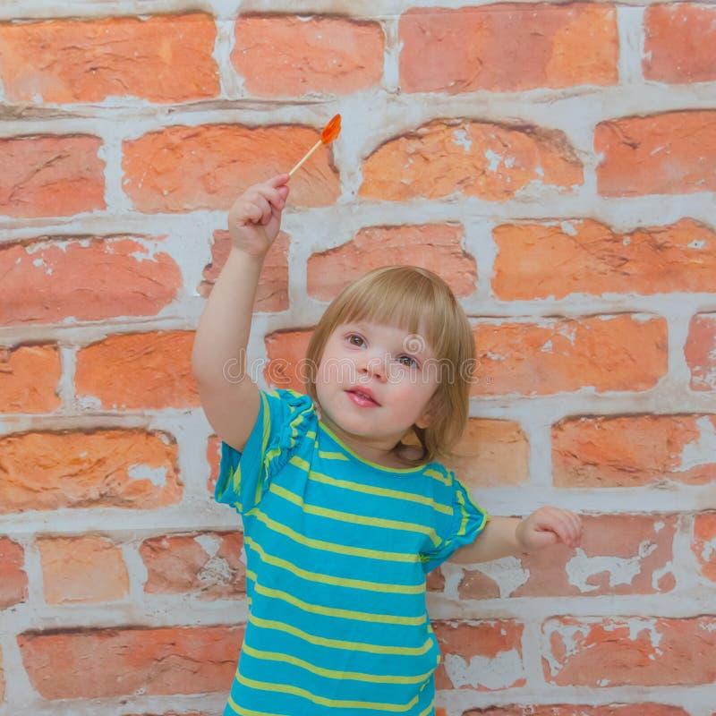 小女孩,婴孩用在棍子的糖果,在砖墙背景 免版税库存图片