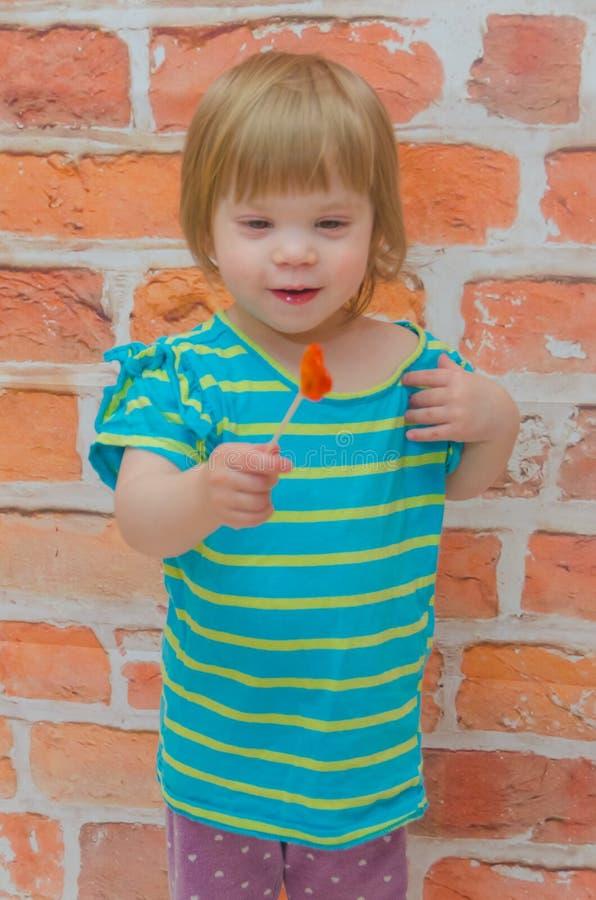 小女孩,婴孩用在棍子的糖果,在砖墙背景 库存图片