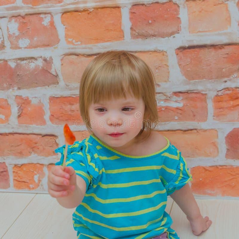小女孩,婴孩用在棍子的糖果,在砖墙背景 库存照片