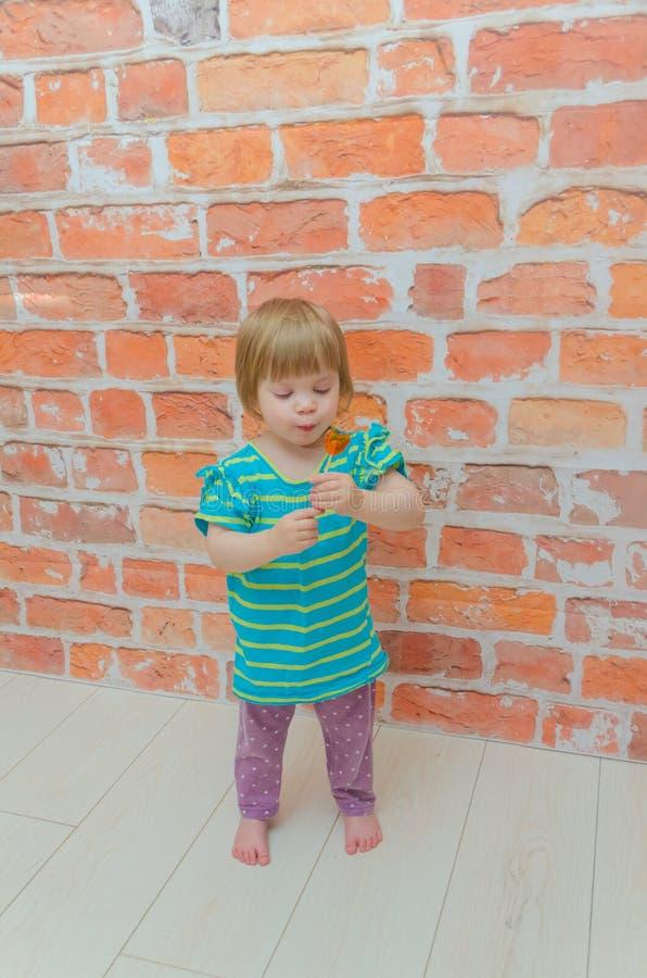 小女孩,婴孩用在棍子的糖果,在砖墙背景 免版税库存照片