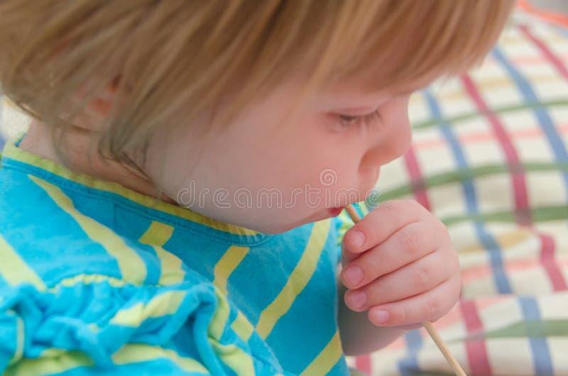 小女孩,婴孩用在棍子的糖果 库存照片