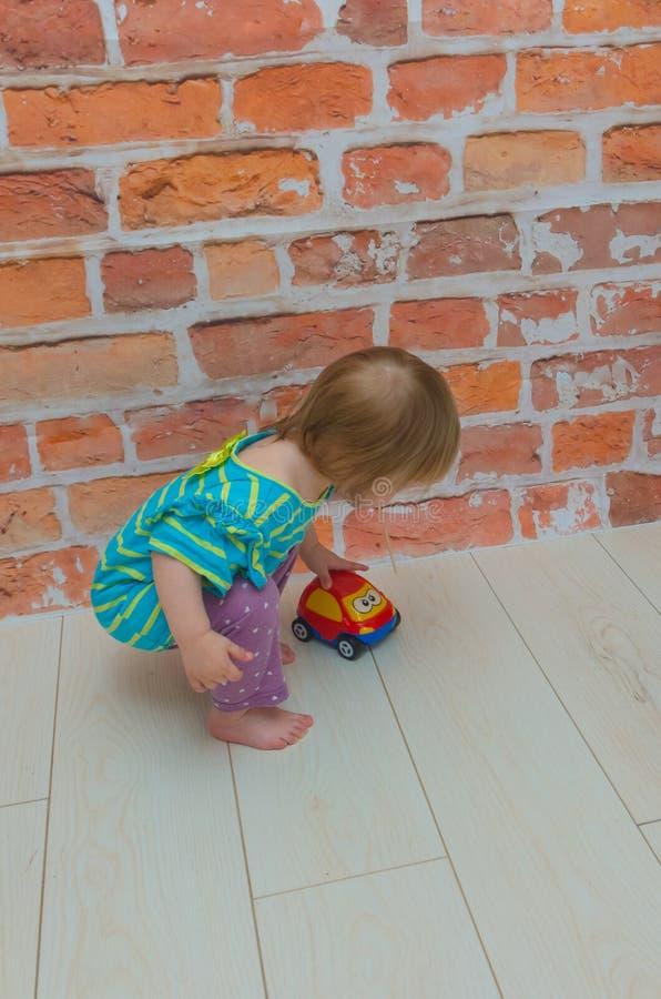 小女孩,有红色汽车的婴孩 免版税库存图片