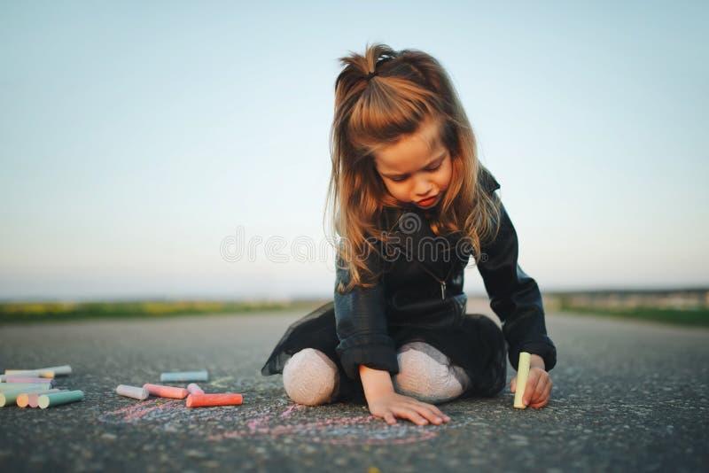 小女孩画在沥青的图片 库存照片