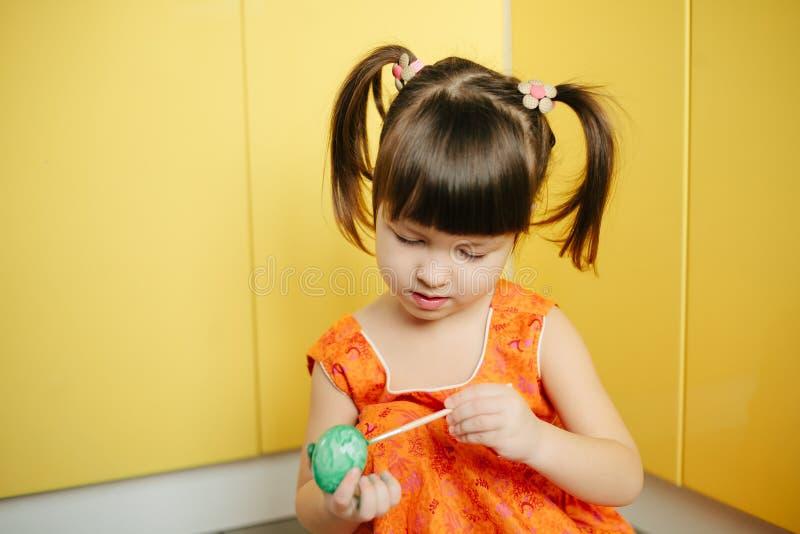 小女孩(孩子)油漆复活节彩蛋 图库摄影
