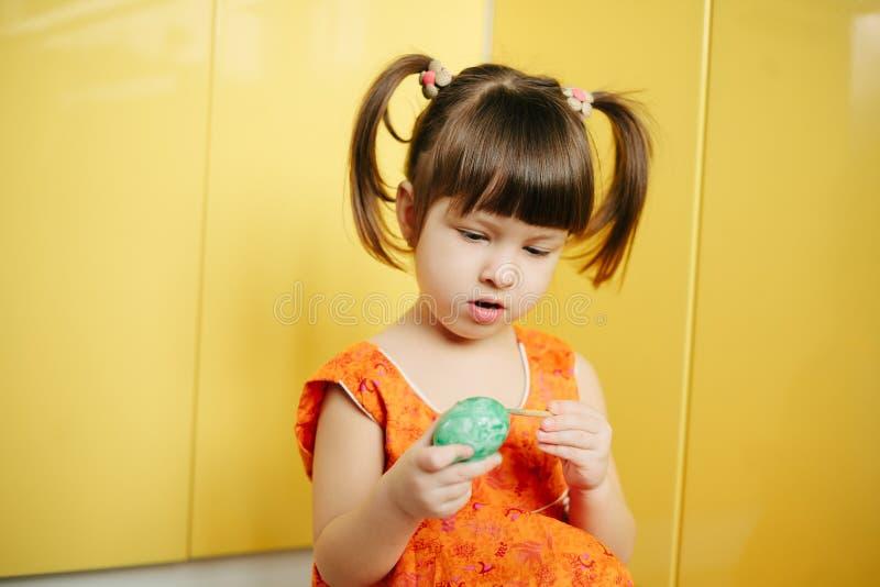 小女孩(孩子)油漆复活节彩蛋 库存照片