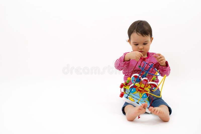 小女孩满意对在白色背景隔绝的五颜六色的木玩具 免版税库存图片