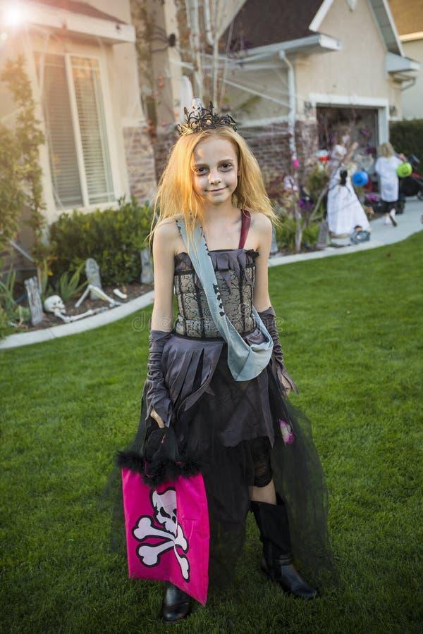 小女孩去的把戏或款待在她的服装的万圣夜 免版税库存图片