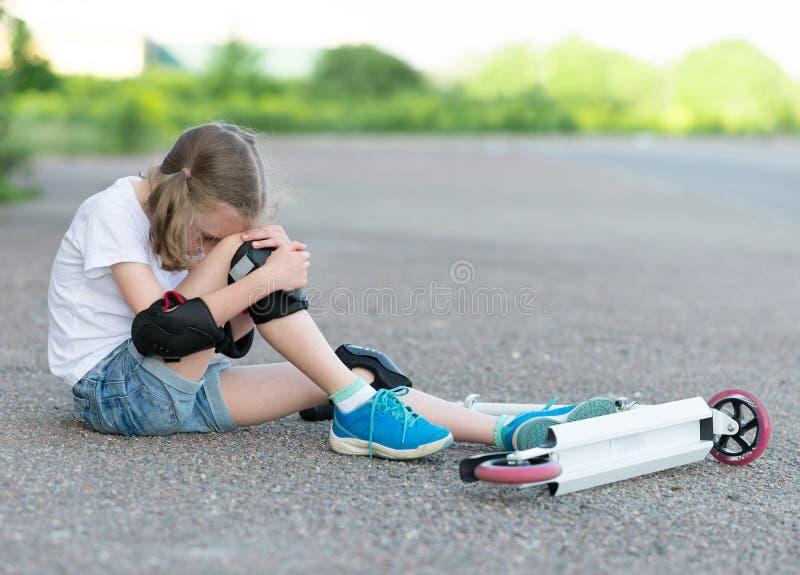 小女孩从滑行车跌倒了 免版税图库摄影