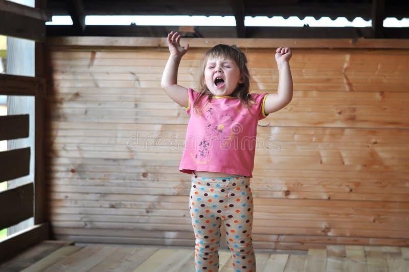 小女孩画象尖叫与眼睛大声关闭了 库存图片