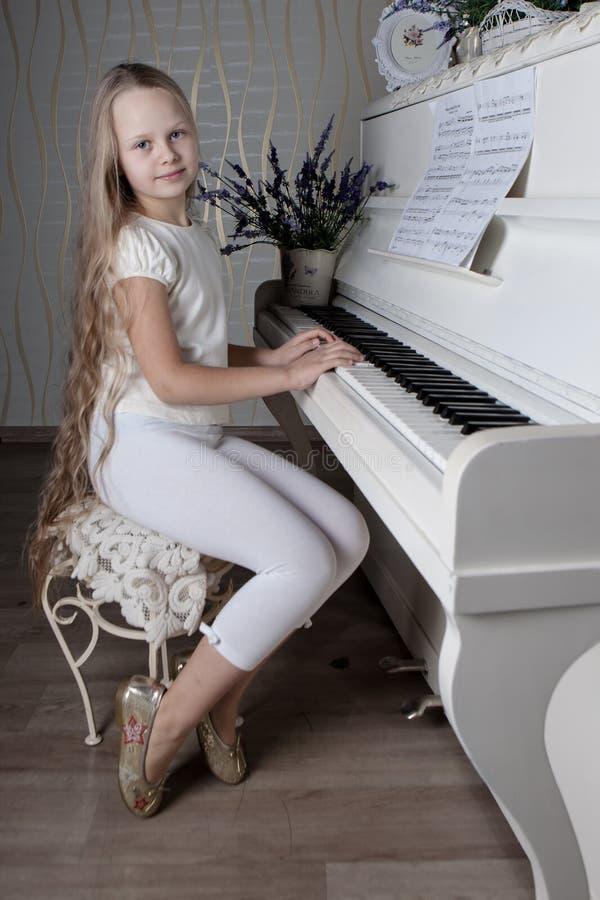 小女孩画象弹钢琴的白色礼服的 图库摄影