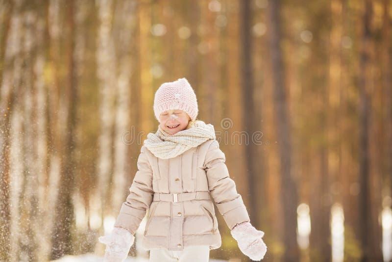 小女孩画象的米黄衣裳使用与雪在一个公园在冬天 库存照片