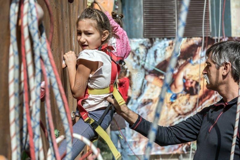 小女婴攀登协助她的墙壁祖父 库存图片