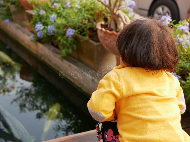 小好奇女婴坐一条小桥梁和观看的游泳的鱼在池塘-小孩的求知欲 免版税库存图片