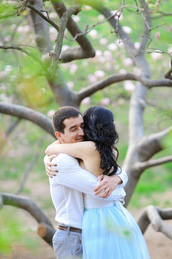 小姐和浅黑肤色的男人在开花的树附近供以人员拥抱 库存照片