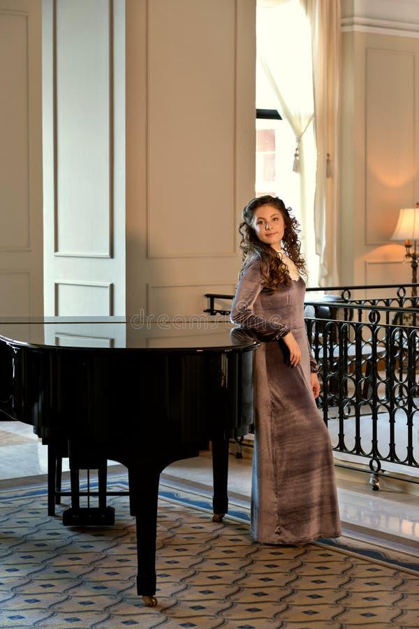 小姐在葡萄酒礼服站立在古板的黑大平台钢琴附近 库存图片