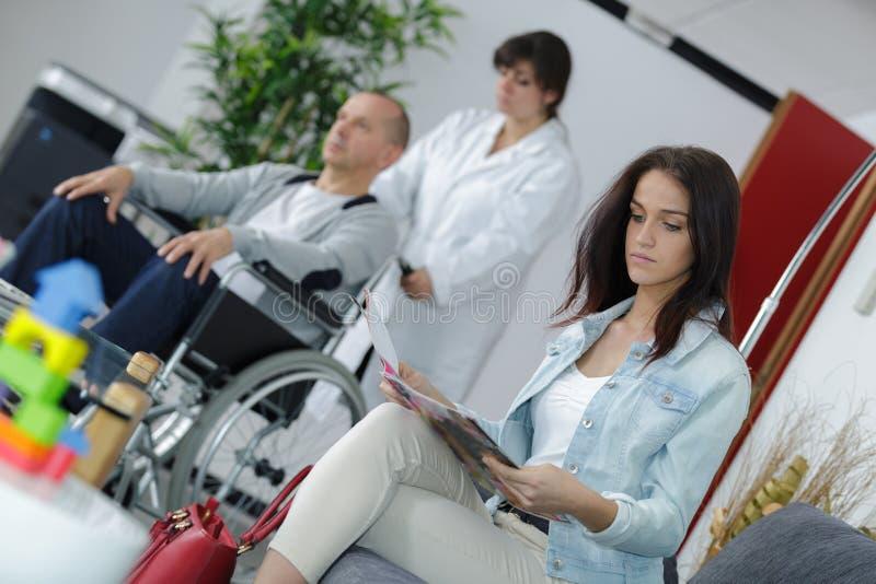 小姐读书杂志,当在医院等候室时 免版税库存照片