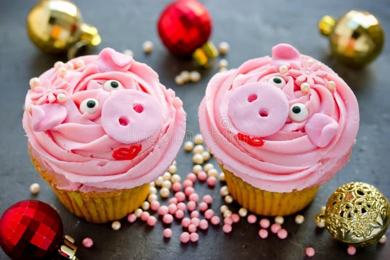 小姐贪心杯形蛋糕-美丽和用桃红色奶油装饰的可口蛋糕塑造了滑稽的贪心面孔 免版税库存图片