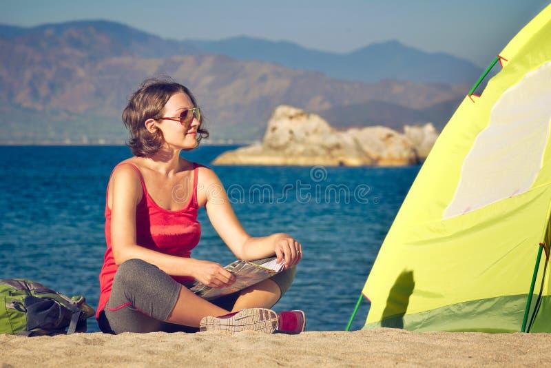 小姐远足者在帐篷和看附近坐海风景 库存图片