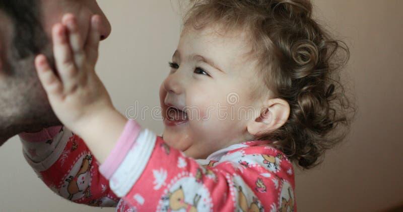 小婴孩在人` s面孔上把他的手放 库存照片